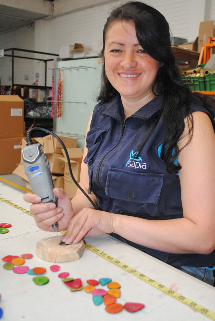 Claudia Zambrano, artisan, is wearing a Sapia vest, working in a workshop at a table. She is using an electric drill on bright pieces of tagua. She is smiling at the camera.