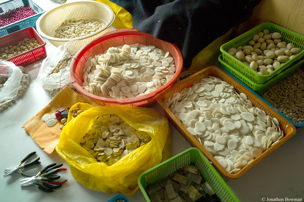 Image shows many different baskets and bags full of tagua nut cut into jewelry shapes. It is still its natural color because it has not yet been dyed.