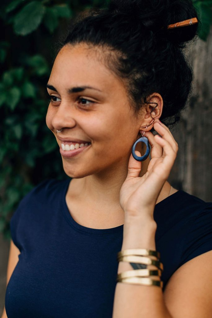 Smiling model with brown skin and black hair shows off her Open Minds Tagua Earrings in Blue--a sustainable jewelry option.