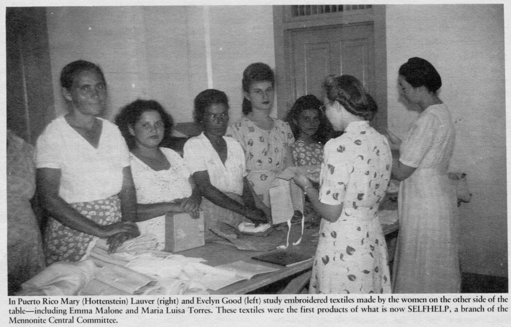 """A newspaper clipping from the 1940s with the caption, """"In Puerto Rico mary Hottenstein Lauver (right) and Evelyn good (left) study embroidered textiles made by the women on the other side fo the table—including Emma Malone and Maria Luisa Torres. These textiles were the first products of what is now SELFHELP, a branch of the Mennonite Central Committee."""