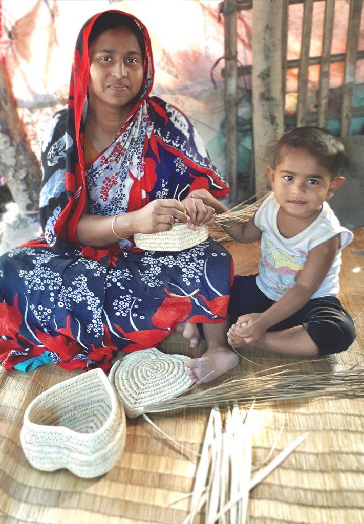 Artisan weaving a palm leaf basket