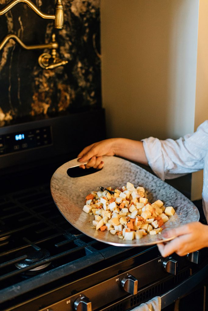 Create a sustainable Christmas by shopping fair trade kitchen items with Ten Thousand Villages. Image shows stuffing in a brushed silver serving platter held over a stove.