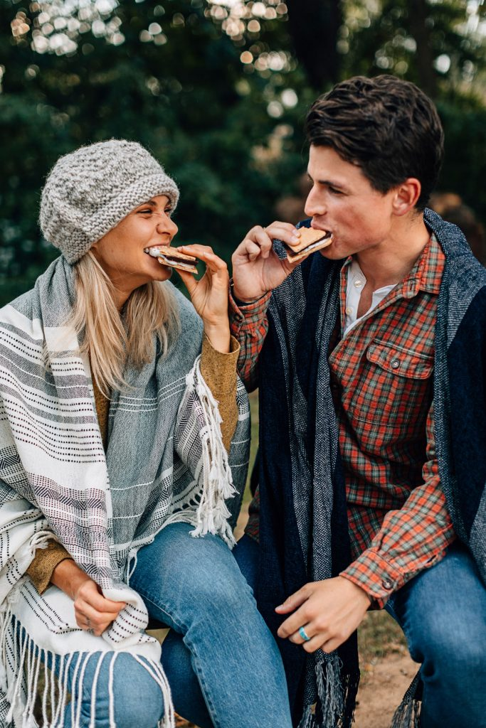 A sustainable Christmas gift idea: give experiences! Image shows two people enjoying s'mores together around a campfire.