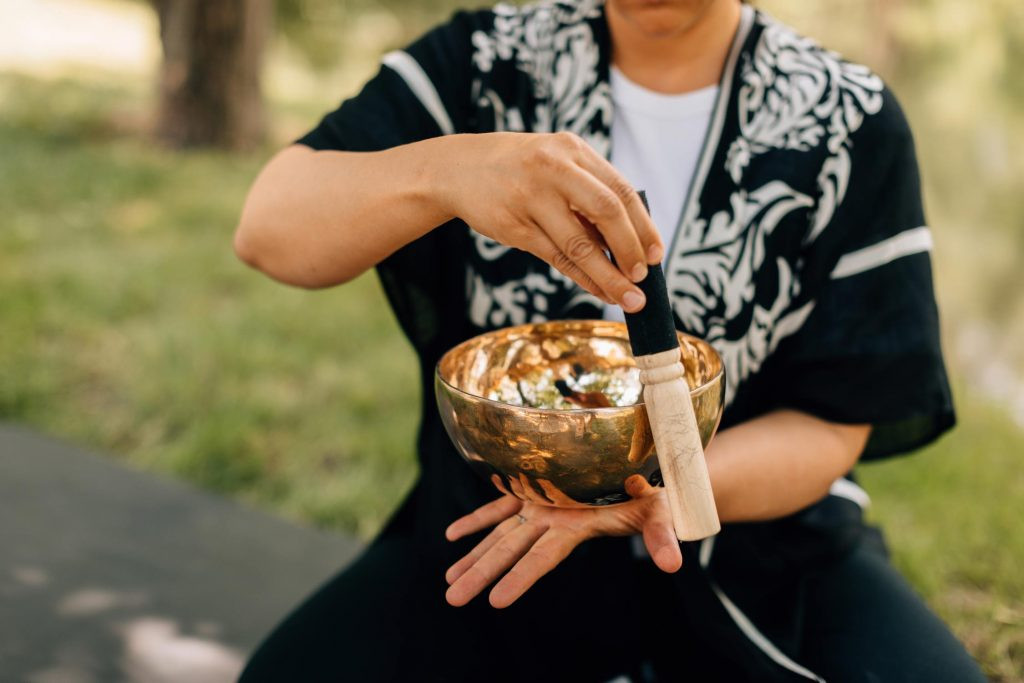 The Inner Peace Singing Bowl is being played by a person in an outdoor setting. They model how to hold the singing bowl flat in their hand, and run the mallet along the outside edge of the bowl with the other hand to produce sound.