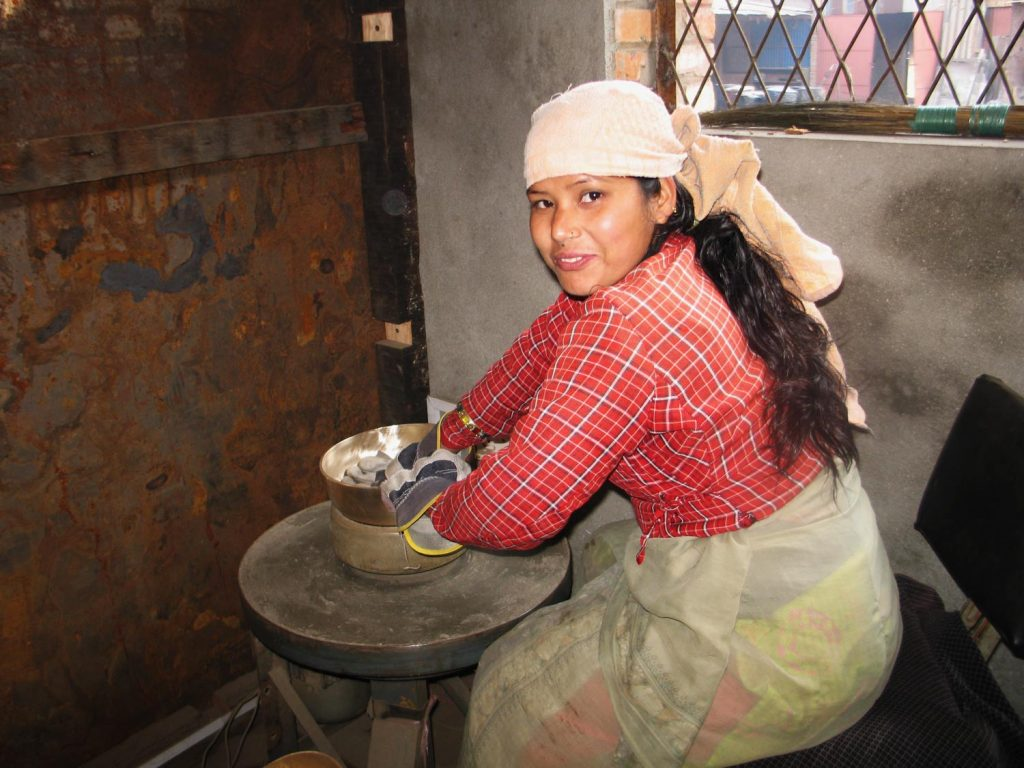 An artisan with long dark hair and a headscarf smiles at the camera. They are wearing leather work gloves and seated at a table where they appear to be polishing a singing bowl. The image was taken in Cottage Craft workshop in Nepal.