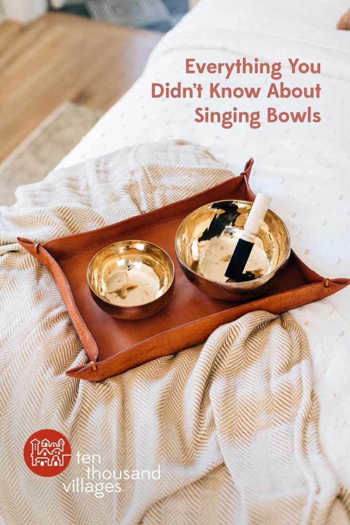 The title, Everything You Didn't Know About Singing Bowls is overlaid on an image of two singing bowls resting on a leather tray at the end of a bed with a white bedding. The singing bowls are shiny with hammered markings and a mallet rests in the larger bowl.