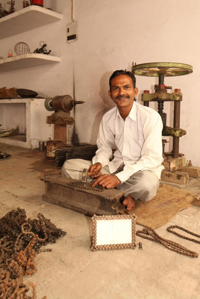 Artisan, Kamrul Hasan, is pictured seated on a mat in a workshop hammering bike chain. He is smiling at the camera and has a product sample of a bike chain picture frame in front of him that he created.