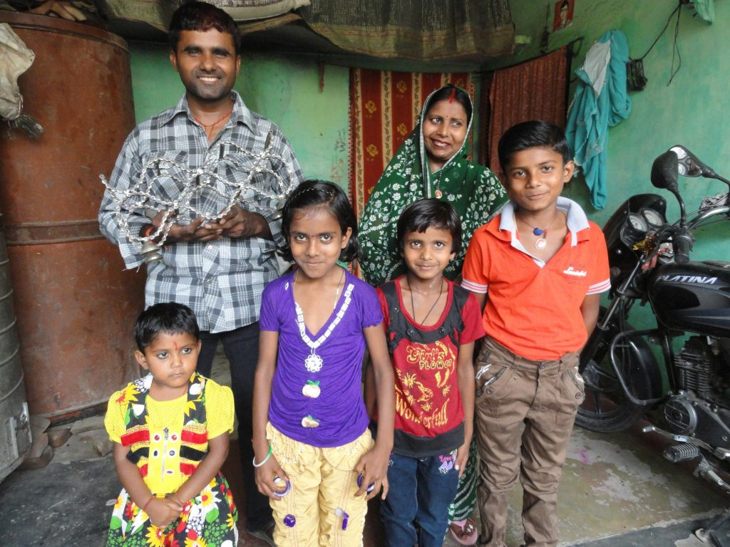 Artisan, Attar Singh and his family are pictured. He stands next to his wife with his four children in front of them. Attar Singh holds up a Bike Chain Wine Rack. There are sari textiles hanging behind them and a motorcycle parked to their right.