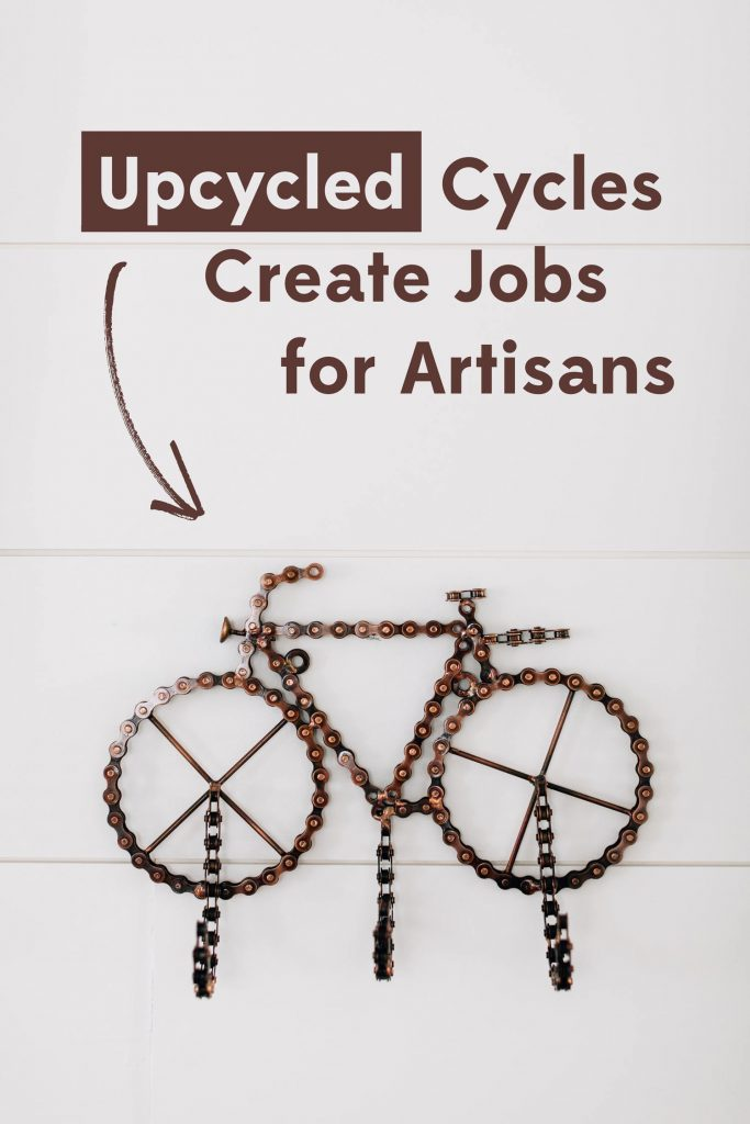 Upcycled Cycles Create Jobs for Artisans headline on a photo of a piece of upcycled bicycle chain art. The bicycle chain has been shaped into a bike with three hooks on it so it functions as hanging wall hooks.