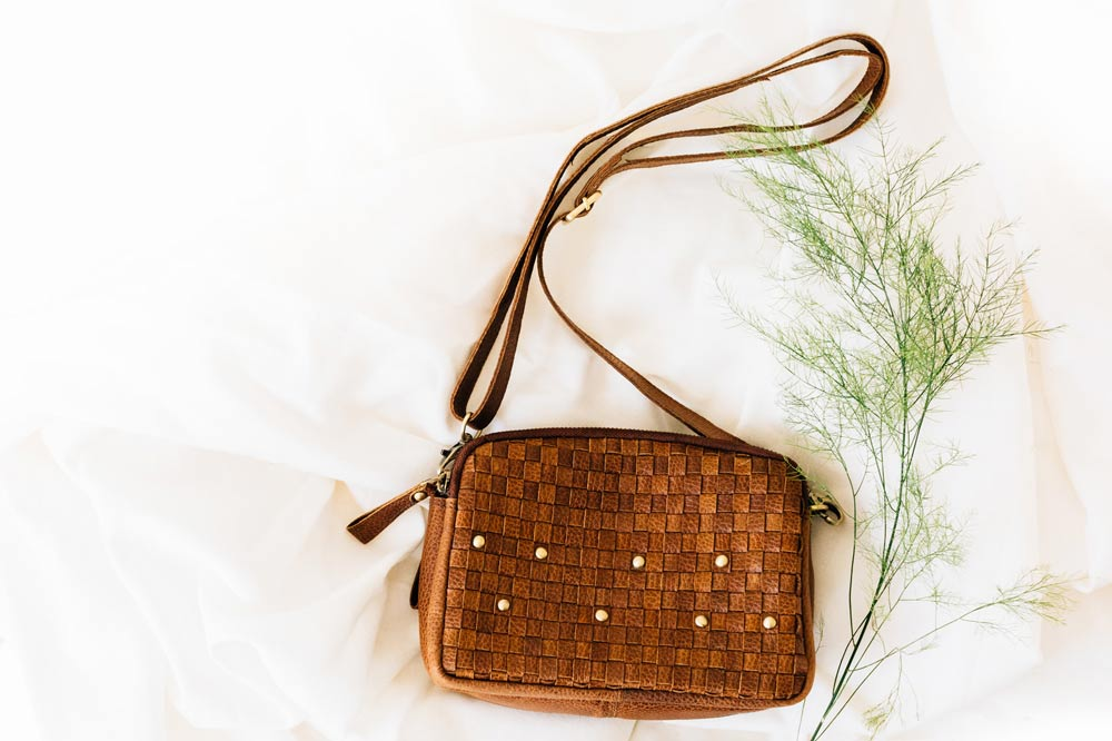 Summer 2021 Fashion Trend: The Eco-Leather Woven Purse, a brown leather woven purse with brass accents lies on linens with a sprig of greenery.