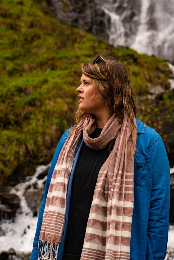Model looks off in the distance wearing the Jamdani Weave Scarf around her neck over a blue chambray shirt. Waterfalls crash behind her.