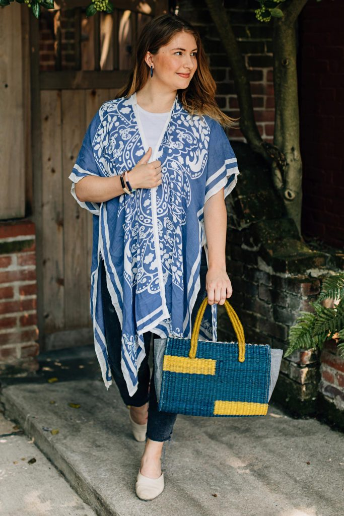 Model wears the Damask Print Wrap in this summer 2021 fashion trend. She appears to be walking with the wrap flowing around her with the Sunbeam Purse in her left hand.