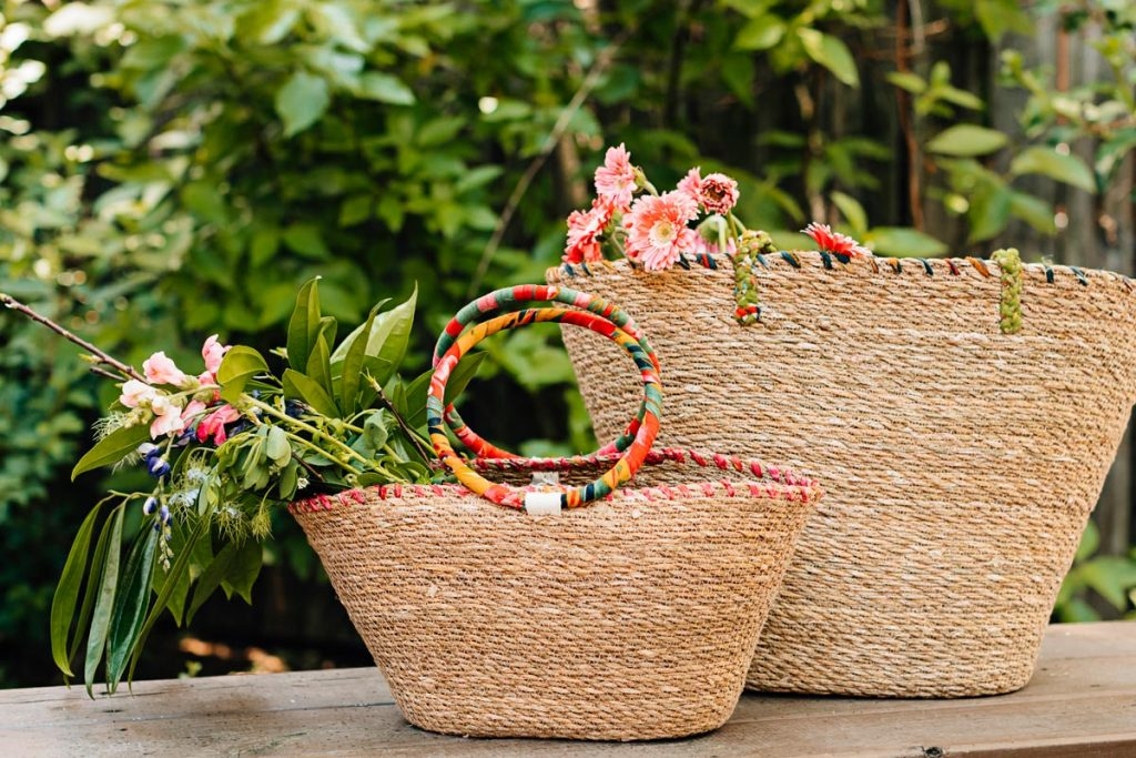 Trend-forward woven bags sit one in front of the other with fresh flowers in them. Handwoven bags with natural grasses and upcycled sari.