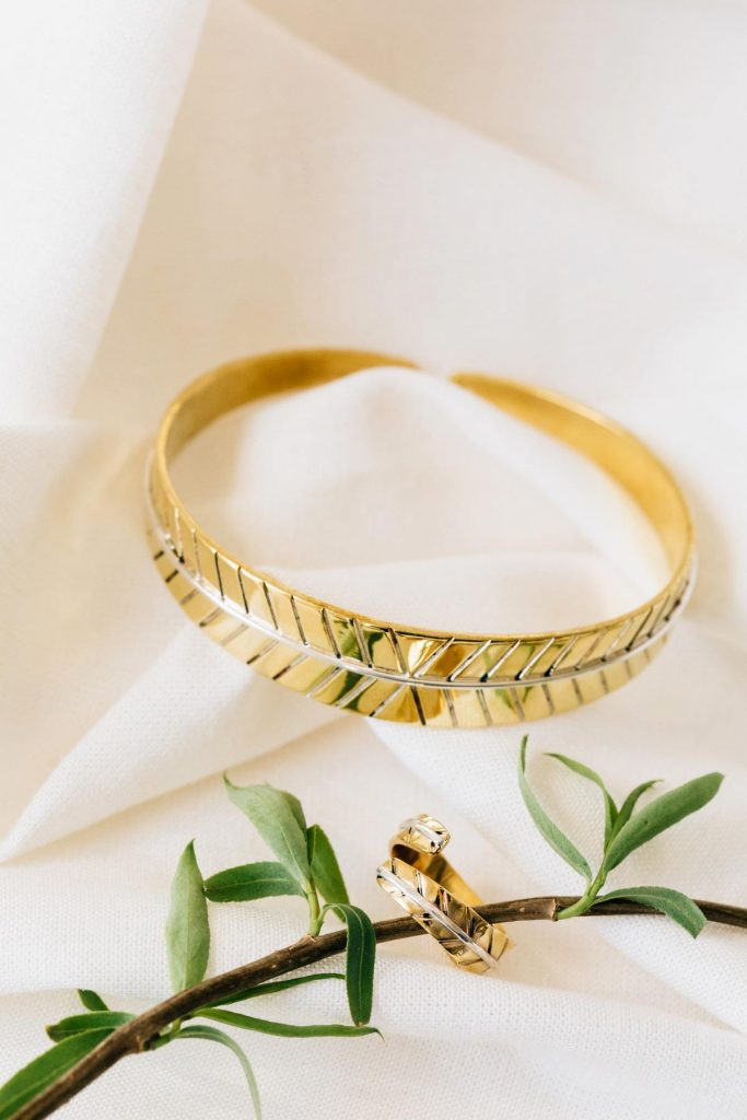 Bombshell Jewelry pieces, Leaf Ring and Leaf Cuff are pictured with an herb sprig on a white background.