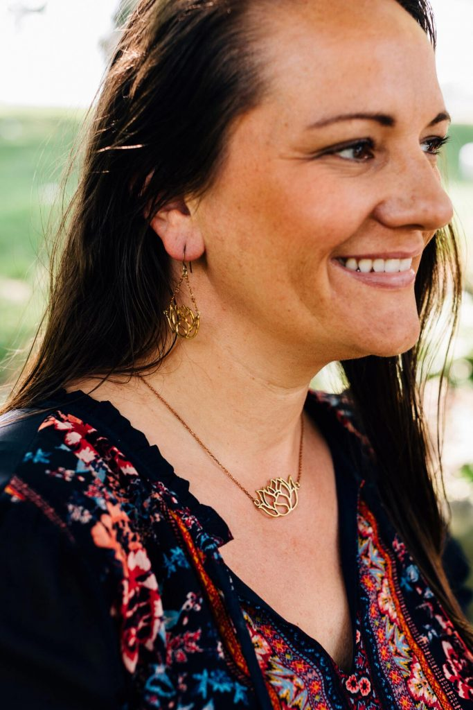Bombshell Jewelry pieces, The Graceful Lotus earrings, and The Graceful Lotus necklace are pictured on a model with long dark hair. She is smiling and looking off in the distance.
