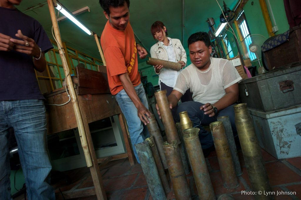 In a workshop in Cambodia, 4 members of the Rajana Association stack and inspect salvaged bomb shells. They are brass and 2-3 feet long.