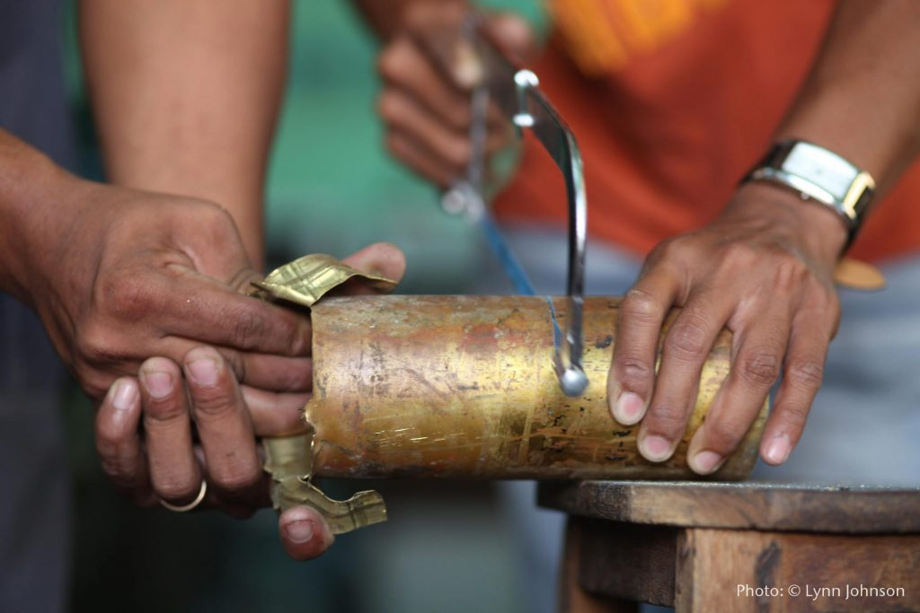 Two artisans work together to cut brass pieces off a bombshell to be melted down and turned into jewelry. Image shows one person's hands holding down the bombshell and sawing through it, while another set of hands peels pieces of brass metal away that have been cut.