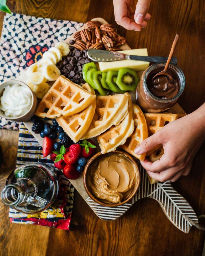 Image is of a brunch board on the Minimalist Serving Board from Ten Thousand Villages. A hand reaches for waffles that are surrounded by berries, kiwi slices, peanut butter, cocoa spread, banana slices, chocolate chips and butter with the Butter Together Knife.