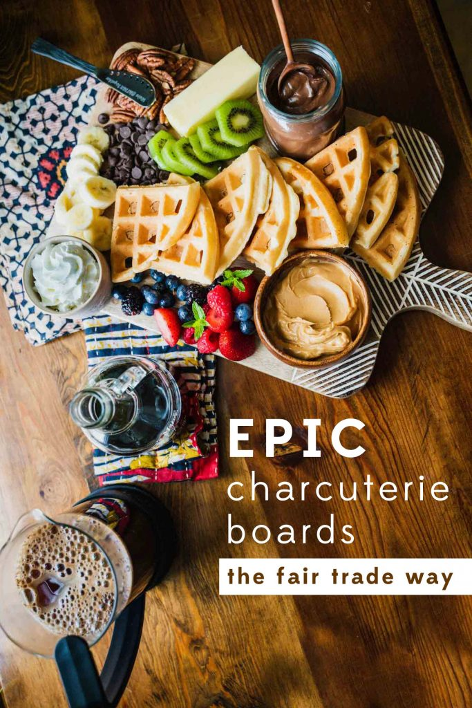 Image of the Minimalist Serving Board with hand etching covered with waffles, fruit and condiments. Text reads, Epic Charcuterie Boards the Fair Trade Way.
