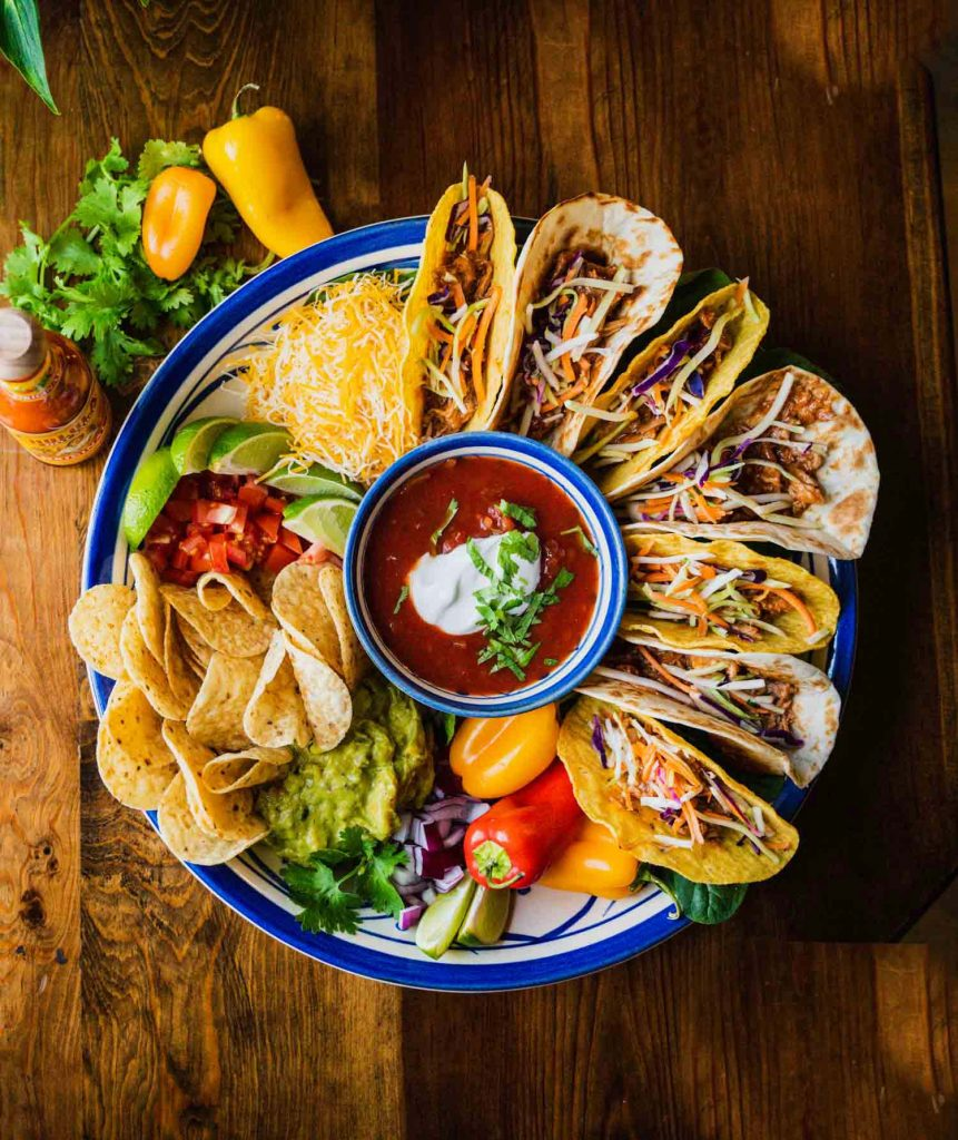 A taco board on the Lovely Leaves Bowl with the Flower Petals Bowl in the center full of salsa. Tacos, peppers, tortilla chips, guacamole, limes and shredded cheese surround the edges of the deep dish.