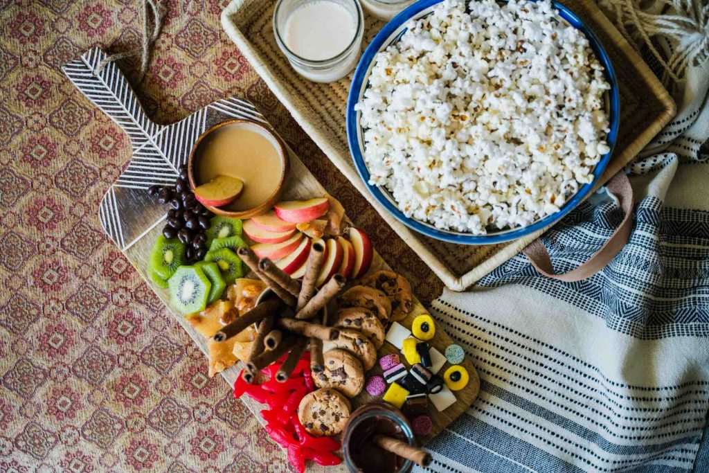 The Movie Night Board is an epic charcuterie board built on the Minimalist Serving Board from Ten Thousand Villages. Fruits, candies and cookies adorn the board next to the Rectangle Handled Basket that hosts a bowl of popcorn in the Bouquet Bowl.