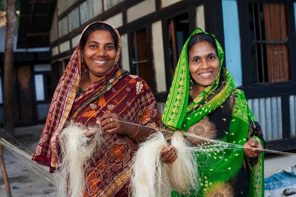 Rasida Begum (left), Manoyara Begum (right) Artisans at Baghda Enterprise (a workshop of Prokritee) in Agailjhara, Barishal, Bangladesh hold strands of thin hemp thread as it's being woven. They are dressed in brightly colored saris and smiling together.