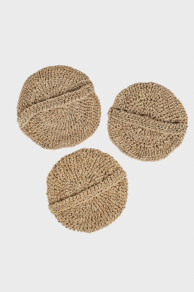 Three hemp scrubbers, a sustainable hemp product, lie on a white background. They have crocheted handles on the back for your hand to slip through.