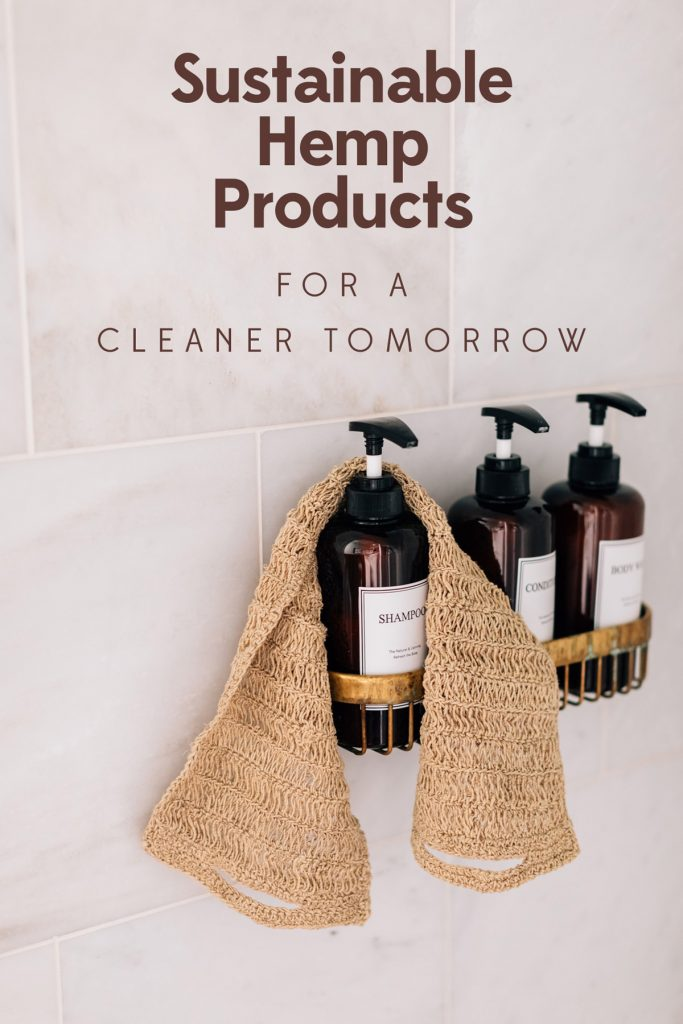 Image ID: The Hemp Back Scrubber rests wrapped around one of three brown glass bath products (shampoo, conditioner, body wash) in a brass holder on the side of a shower.  Text on image reads: Sustainable Hemp Products for a Brighter Tomorrow.