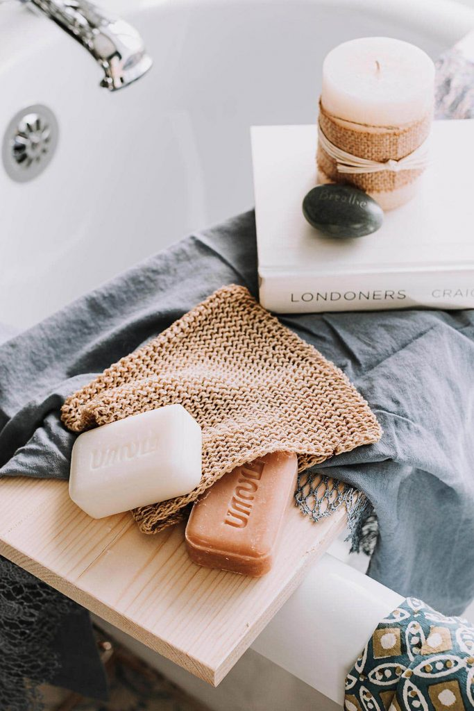 The Natural Hemp Washcloth, a sustainable hemp product, lays tub-side with two bars of handcrafted soap from Ten Thousand Villages.