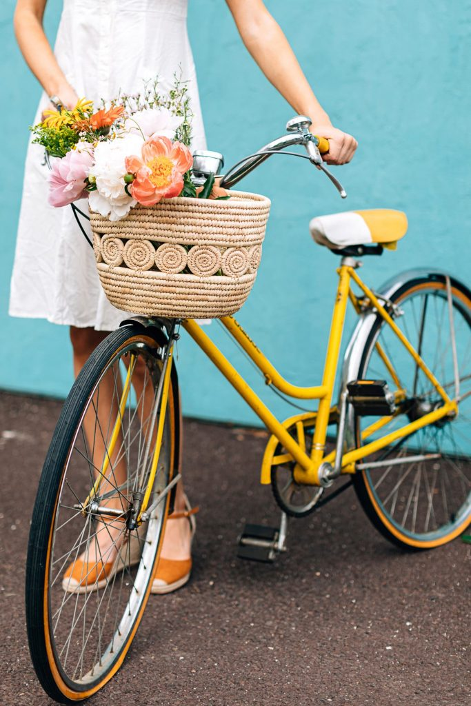 The Palm Leaf Bike Basket by Ten Thousand Villages is shown on the front of a yellow vintage Schwinn bicycle with a fresh flowers bouquet in it. A person in a white dress stands next to it holding the handlebars in front of a cyan blue wall.