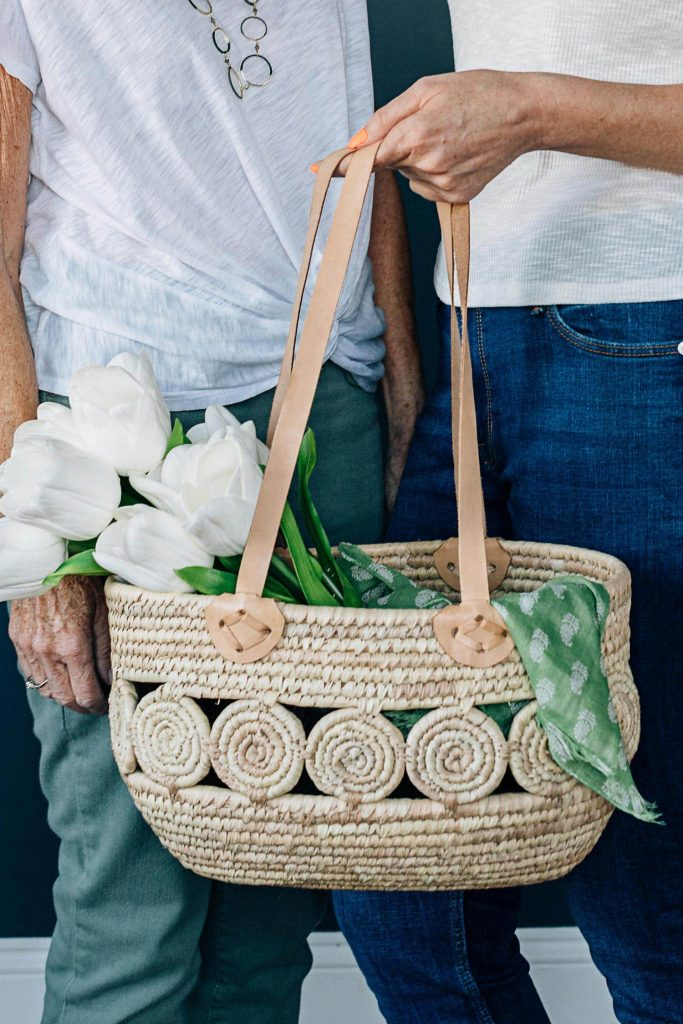 Two people stand side-by-side, one older, one younger, holding the Essential Companion Tote by Ten Thousand Villages in front of them. Fresh white tulips and a green bandana stick out of the basket.