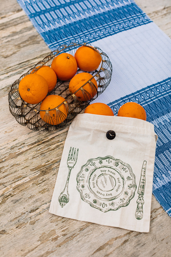 """The Eat Well Produce Sack by Ten Thousand Villages is a cloth produce/bulk foods sack shown here with oranges spilling out. The front has a graphic of a dinner plate that says """"buy fresh, buy local,"""" in between a knife and fork. Show as a plastic sandwich bag alternative for sustainable picnicking."""