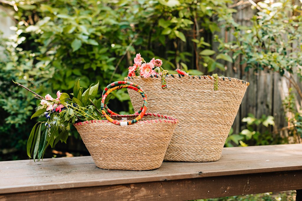 Two woven bags by Ten Thousand Villages with recycled sari accents stand together in a garden with fresh flowers sticking out of them.