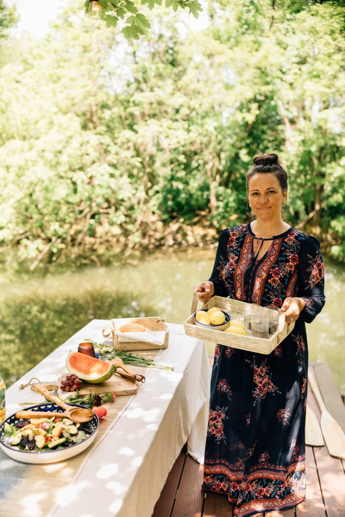 A person in a long dress stands next to a table laid with food. They are outside near a river hosting a sustainable celebration. They're holding a basket tray with glasses of water and lemon on it.