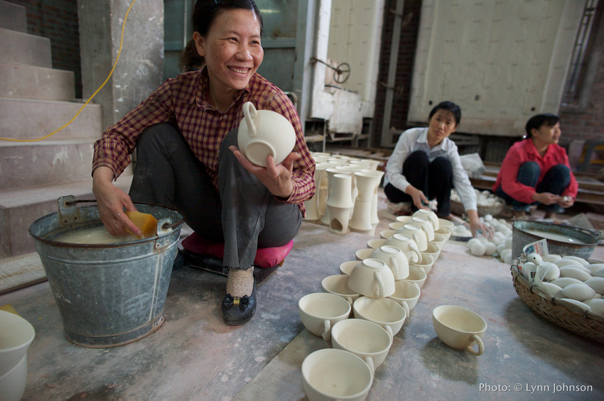 Hoang Thi Minh cleans the rough spots off mugs during ceramic production. She is smiling with two other women working behind her. | Celebrating 75 years of fair trade with Ten Thousand Villages.