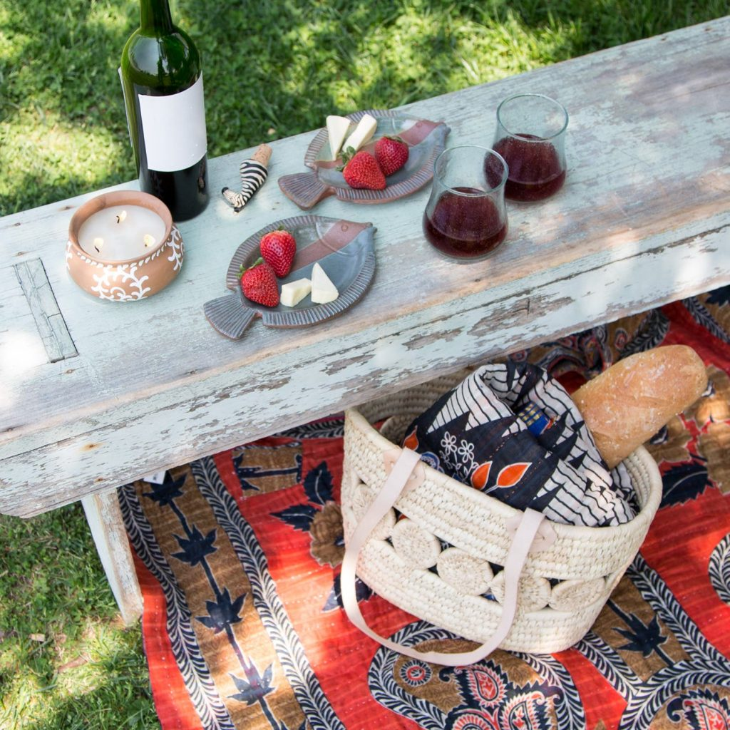 Sustainable picnic fare from Ten Thousand Villages is featured with a recycled sari blanket on the grass, the Essential Companion woven tote on top with another Recycled Sari Throw blanket inside. Picnic food and wine are laid out.