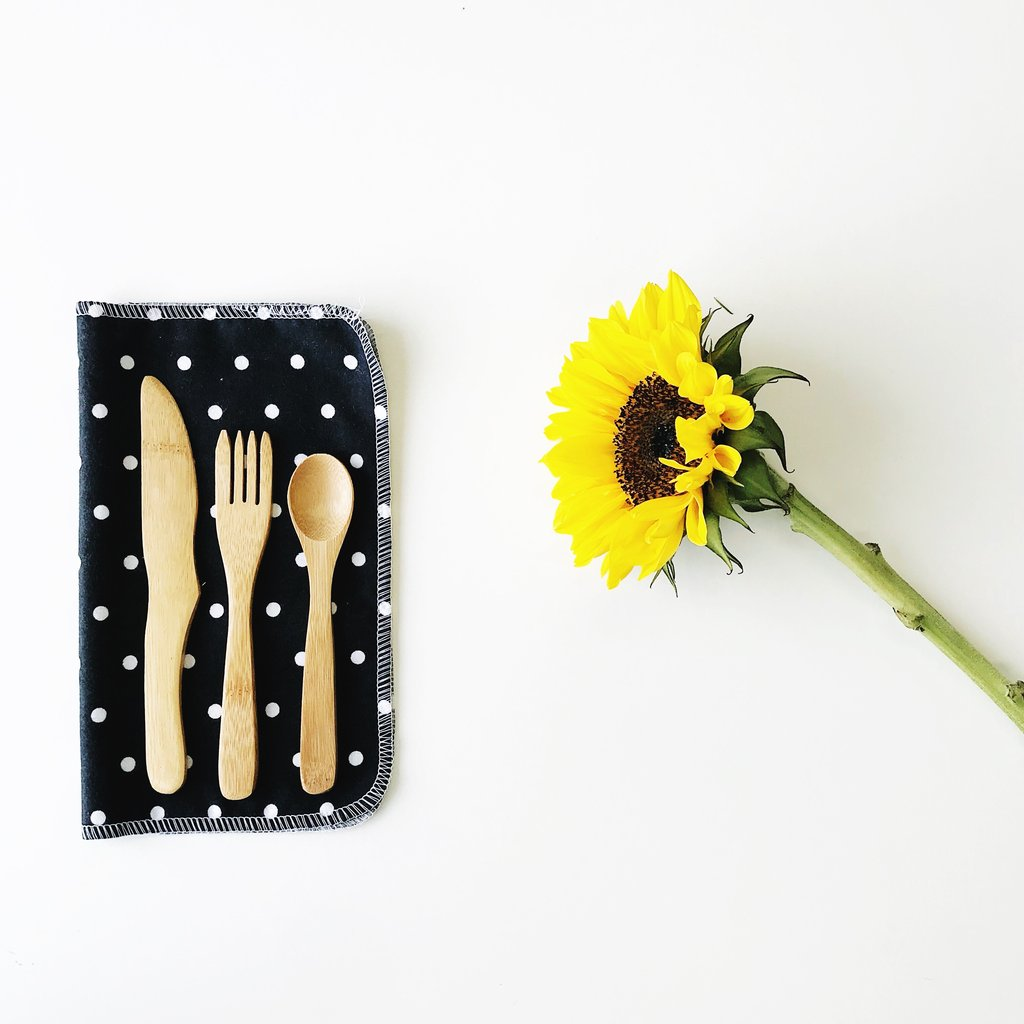Sustainable utensils made from bamboo can replace plastic cutlery.  Try this set from Marley's Monsters featured on a black and white cloth napkin next to a sunflower.