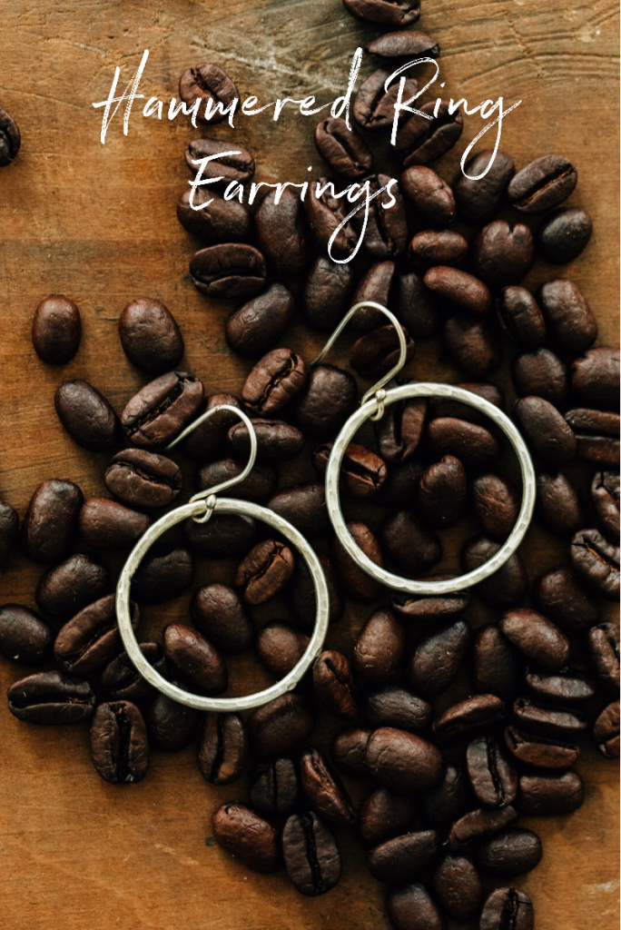Hammered Ring Earrings from Ten Thousand Villages   Handmade fair trade jewelry by artisans of Bombolulu Workshops in Kenya. Earrings lay in scattered coffee beans.