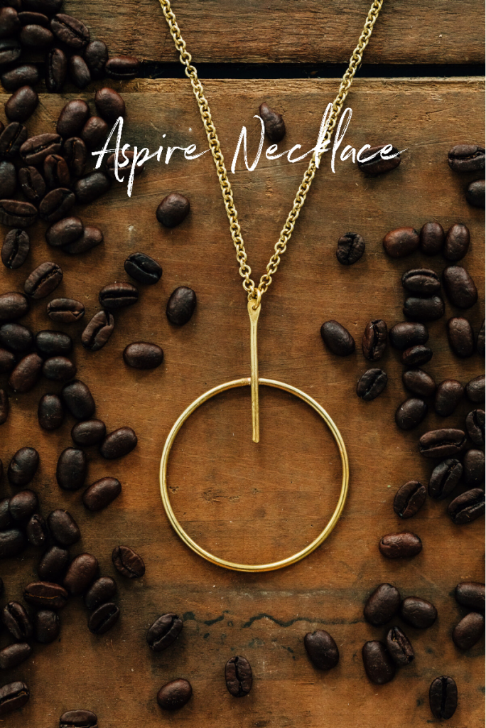 The Aspire Necklace from Ten Thousand Villages   Handmade fair trade jewelry by Bombolulu Workshop artisans in Kenyan lays in scattered coffee beans.